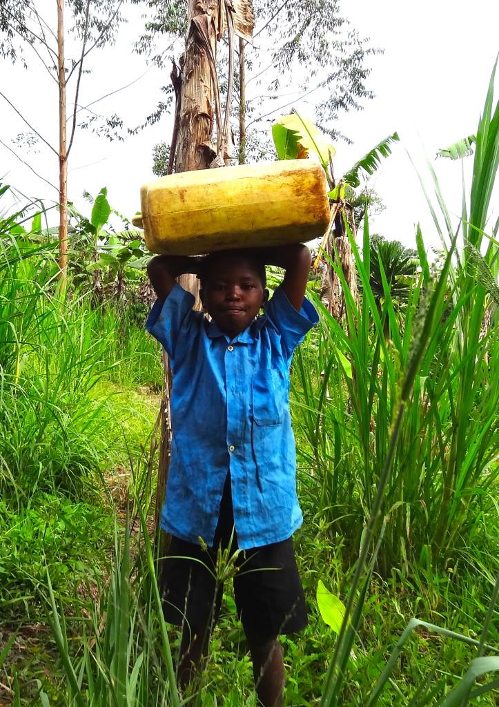 Ein Junge aus der Kigooro-Gemeinde trägt einen 20 Liter Wasserkanister