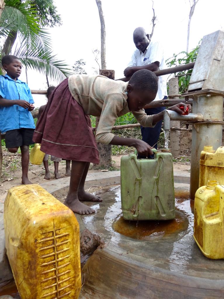 Kinder holen Wasser am Kigooro-Brunnen